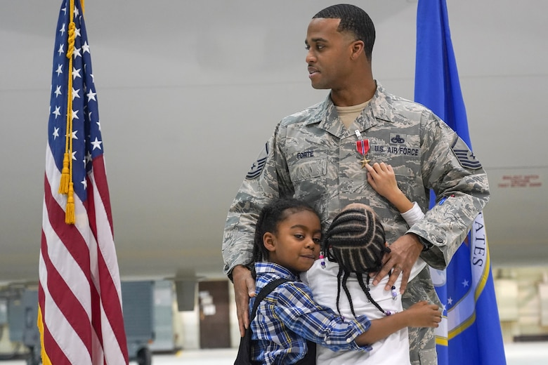 Master Sgt. and his children during a ceremony awarding him the Bronze Star Medal