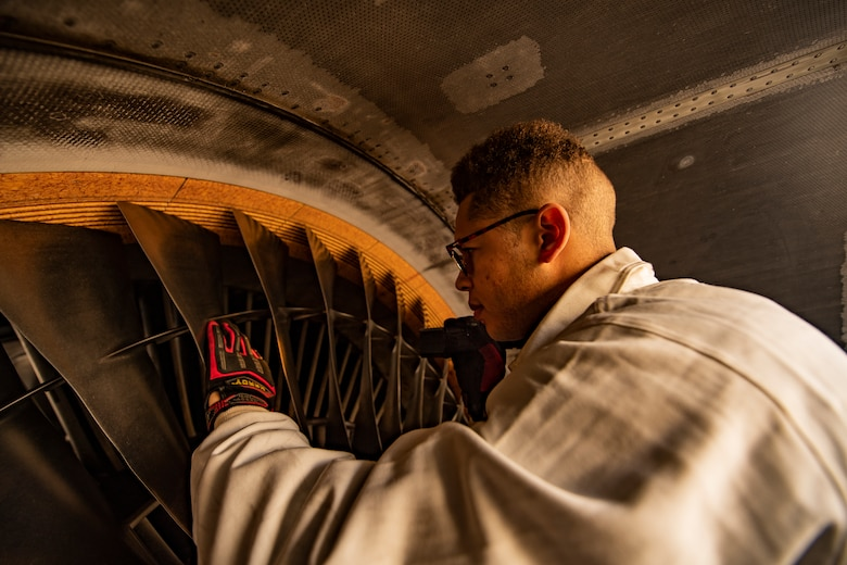 Senior Airman inspects engine blades for deficiencies before an eco-wash