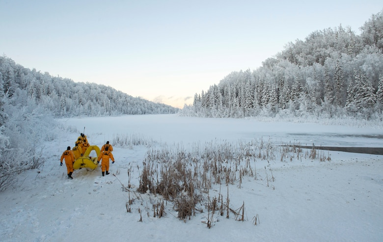 Air Force fire protection specialists make their way toward a frozen lake during ice-rescue training