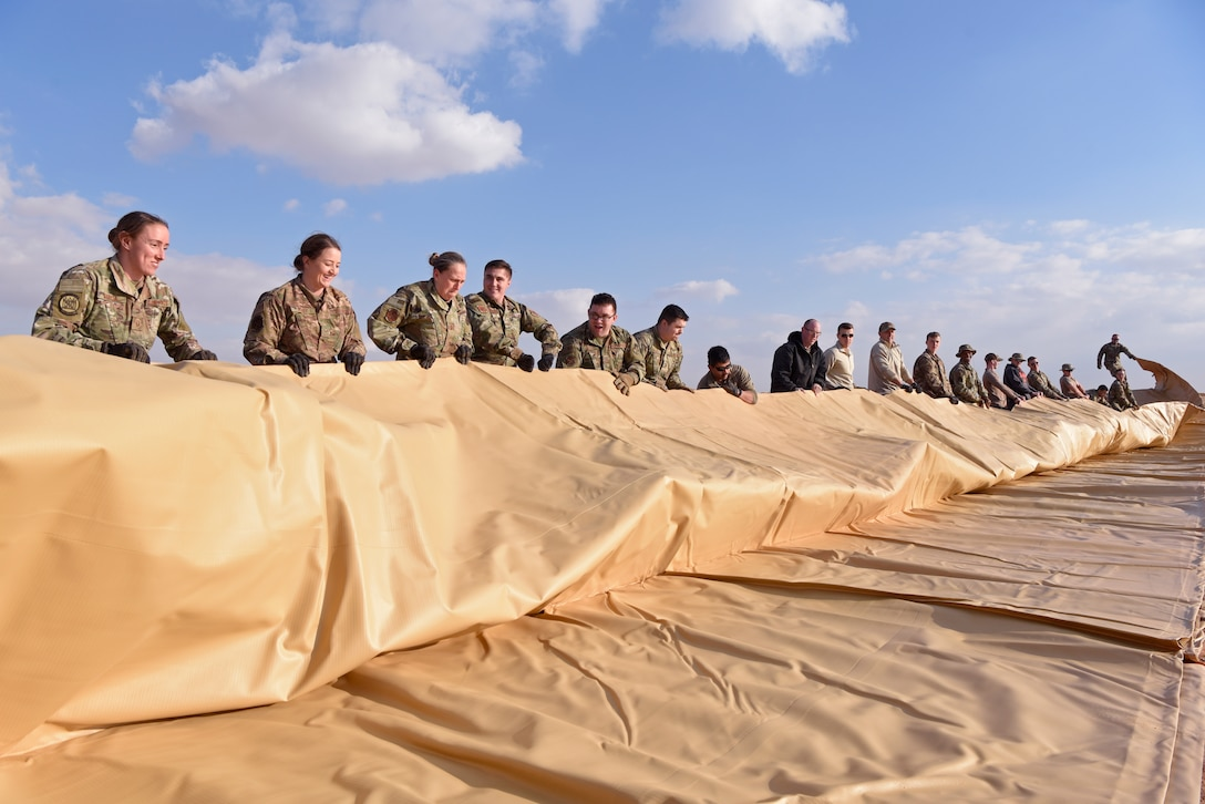 A group of airmen unroll a large fuel bag.