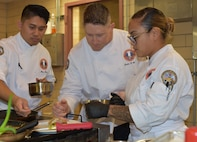 U.S. Army Culinary Arts Team members Staff Sgts.  Marc Susa (left), Justin Chase (center), and Erica Melendres (right), plate a finished dish at a team practice. USACAT will participate in the World Culinary Olympics 2020 in Stuttgart, Germany in February as part of Team USA. (U.S. Army photo by Sarah Hauck)