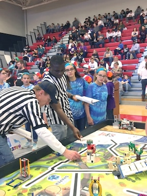 Hypersonic Narwhals team members Karina and Kolleen Roessig, at right, pay close attention as 2nd Lt. Kodjovi Klikan, pictured second from left, an Arnold Engineering Development Complex team member at Arnold Air Force Base, reviews the score with a fellow referee at the regional qualifying tournament at Coffee County Middle School in December. Erin Geraghty and Felicia Goins, the other members of the Hypersonic Narwhals, look on. (Courtesy photo)
