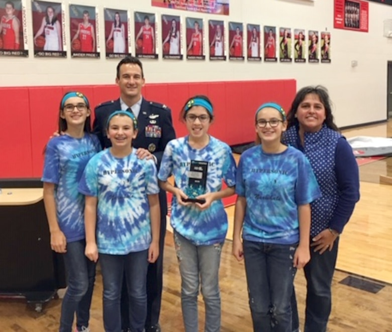 Arnold Engineering Development Complex Commander Col. Jeffrey Geraghty, pictured back left, presents Hypersonic Narwhals team members and Coach Kristeen Roessig, right, with the Champions Award following a FIRST® LEGO® League regional qualifying tournament in December at Coffee County Middle School. (Courtesy photo)