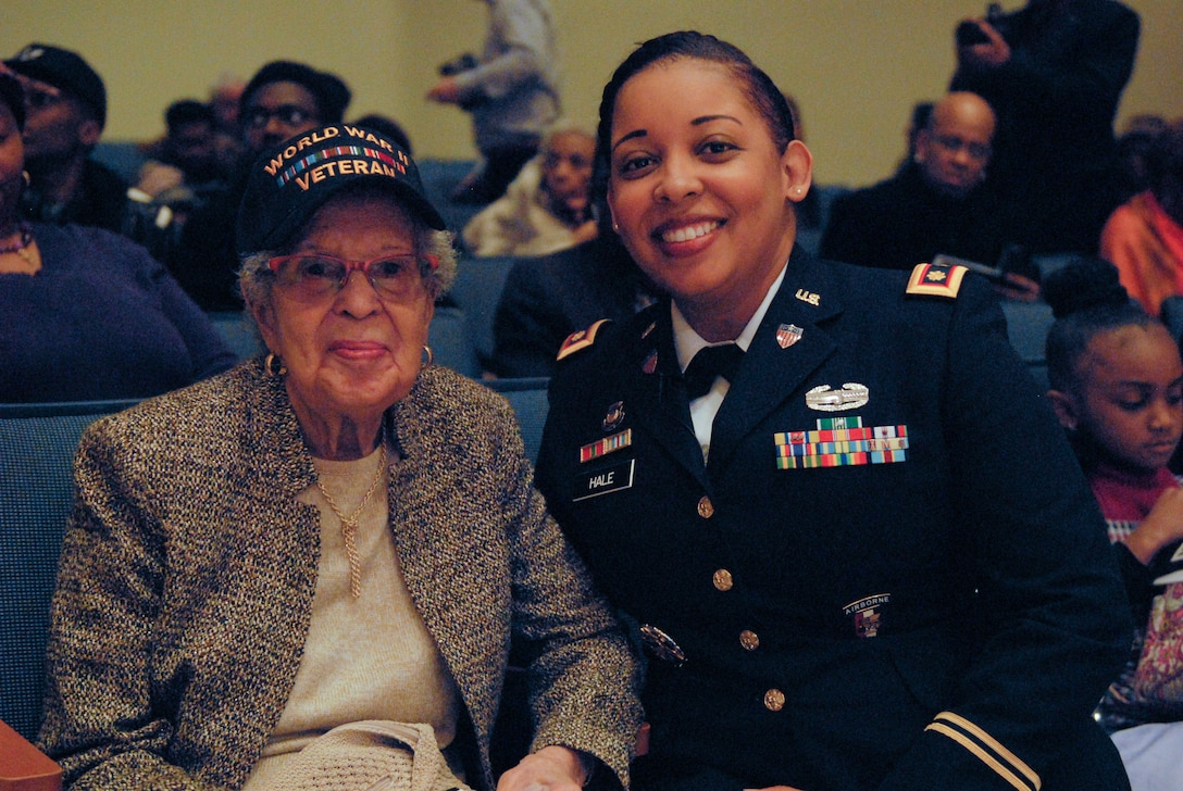 Maj. Lakisha Hale-Earle, chief of G1 plans and training for the U.S. Army Reserve's 99th Readiness Division (right), pays tribute to former Sgt. Hilda P. Griggs, who served in the Second World War's 6888th Central Postal Directory Battalion (left), during New Jersey's annual Martin Luther King Jr. commemoration Jan. 19 at the N.J. State Museum Auditorium in Trenton. The 6888th was the first-and-only all-African American, all-female unit to deploy overseas during the war. It consisted of 855 women under the command of Lt. Charity Adams, the first African-American woman commissioned in the Women's Army Corps.