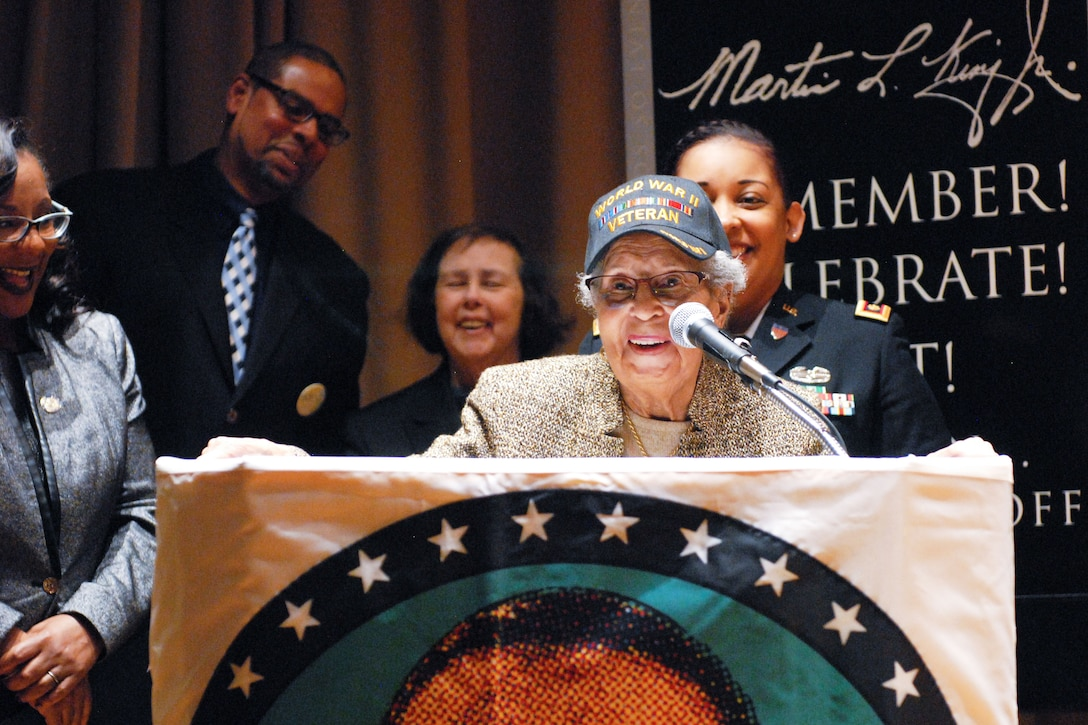 A veteran speaks at a lectern while four other people look on.