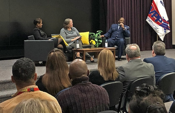 Community leaders sit onstage and talk about leadership.