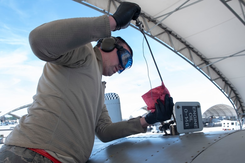 A photo of an Airman placing a dipstick in A-10C Thunderbolt II oil to determine its levels during a joint oil analysis.