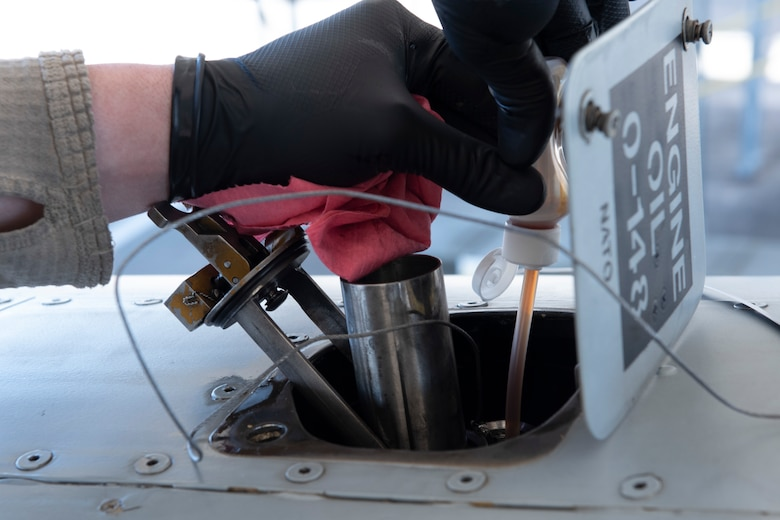 A photo of an Airman extracting oil from an A-10C Thunderbolt II during a joint oil analysis.