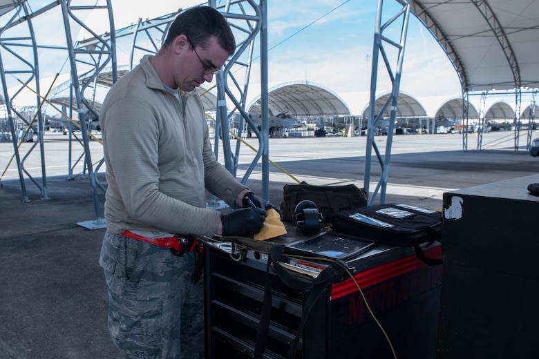 A photo of an Airman packaging oil samples and a form 2026 during a joint oil analysis.