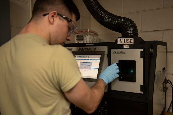 A photo of an Airman burning aircraft oil in a spectrometer.