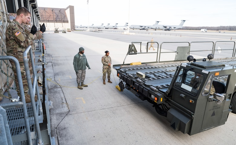 Members of the 436th Aerial Port Squadron instruct Army personnel on proper pallet loading onto a 60-ton K-loader Jan. 10, 2020, on Dover Air Force Base, Del. In a scheduled joint partnership training event, 16 members from the 622nd Movement Control Team, Joint Base Langley-Eustis, Va., came to Dover AFB for cargo and personnel processing training. (U.S. Air Force photo by Roland Balik)