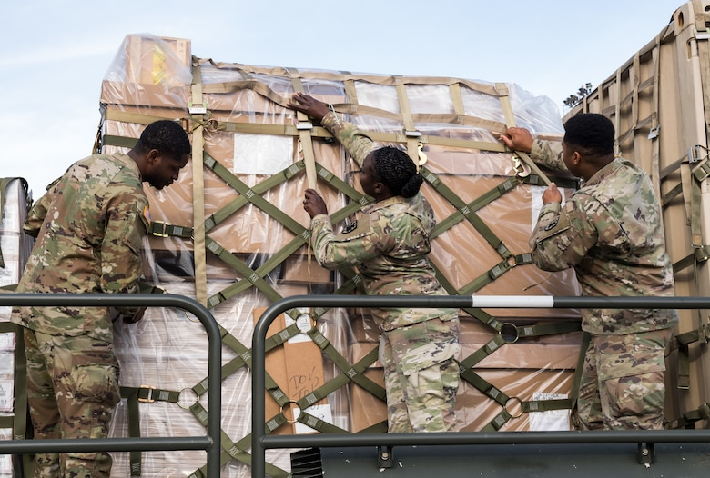Members of the Army's 622nd Movement Control Team, Joint Base Langley-Eustis, Va., secure cargo netting Jan. 10, 2020, on Dover Air Force Base, Del. In a scheduled joint partnership training event, 16 members from the 622nd MCT came to Dover AFB for cargo and personnel processing training. (U.S. Air Force photo by Roland Balik)