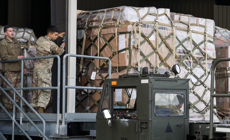 Air Force Staff Sgt. Kenneth Buckley, 436th Aerial Port Squadron assistant reserve coordinator, observes Pfc. Enrique Cubasanche, 622nd Movement Control Team movement specialist, Joint Base Langley-Eustis, Va., load a cargo pallet onto a 60-ton K-loader Jan. 10, 2020, on Dover Air Force Base, Del. In a scheduled joint partnership training event, 16 members from the Army's 622nd MCT came to Dover AFB for cargo and personnel processing training. (U.S. Air Force photo by Roland Balik)