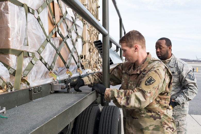 Air Force Master Sgt. Gerard Carry, 436th Aerial Port Squadron ramp operations noncommissioned officer in charge, observes Army 2nd Lt. Mackenzie Ferguson, 622nd Movement Control Team movement officer, Joint Base Langley-Eustis, Va., engage a cargo pallet lock on a 60-ton K-loader Jan. 10, 2020, on Dover Air Force Base, Del. In a scheduled joint partnership training event, 16 members from the 622nd MCT came to Dover AFB for cargo and personnel processing training. (U.S. Air Force photo by Roland Balik)