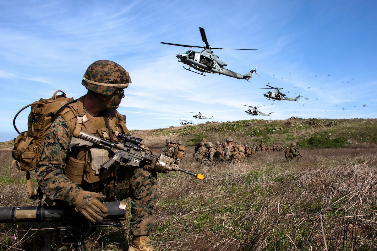 Marines watch as a group of helicopters prepare to land.