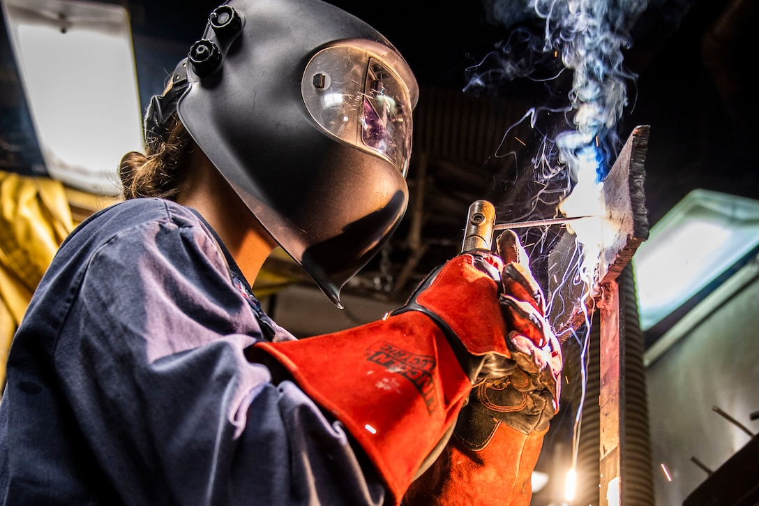 Sparks fly as a sailor wearing a helmet welds metal on a ship.