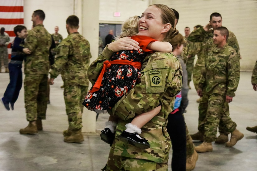 A soldier smiles brightly as she hugs her small daughter during a homecoming ceremony.