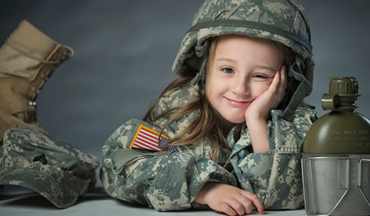A young girl holds her face with her hand as she wears her father's Army combat uniform and helmet. A boot, cap and canteen sit beside her.