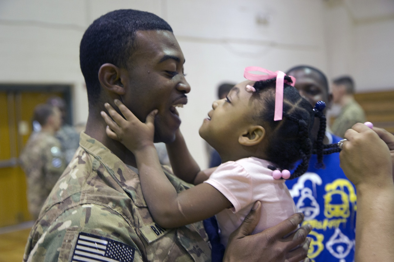 A little girl wearing a pink shirt and hair bow holds her smiling dad's face as they embrace.