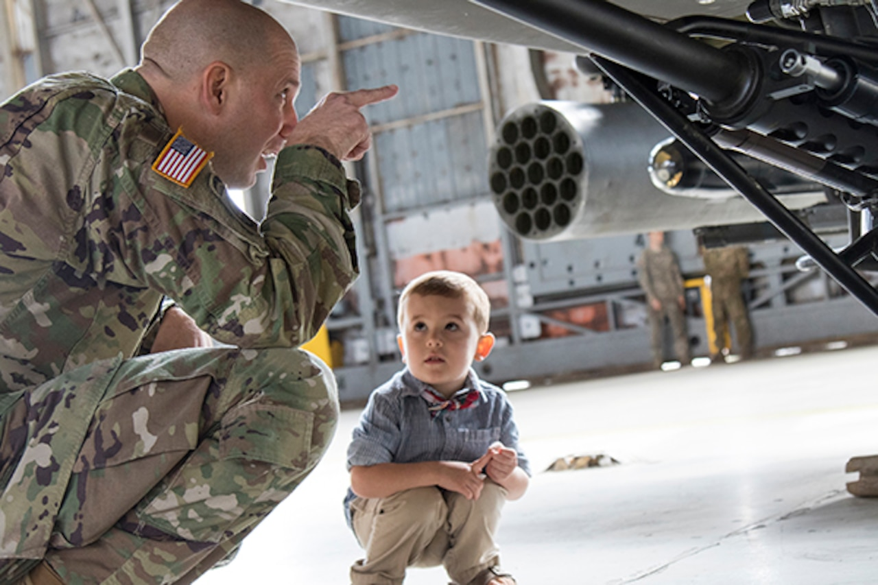 A squatting soldier points to something on the bottom of an airplane as a little boy, also squatting, looks at the soldier.