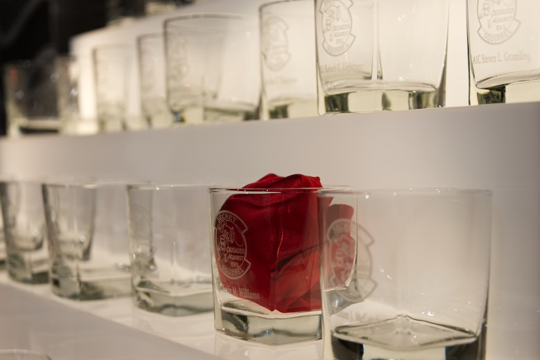 Secret Squirrel drink glasses lined up.  One has red rag stuffed in it.
