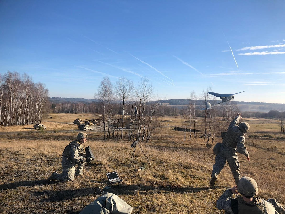 A soldier kneels on the ground as another throws an aerial device.