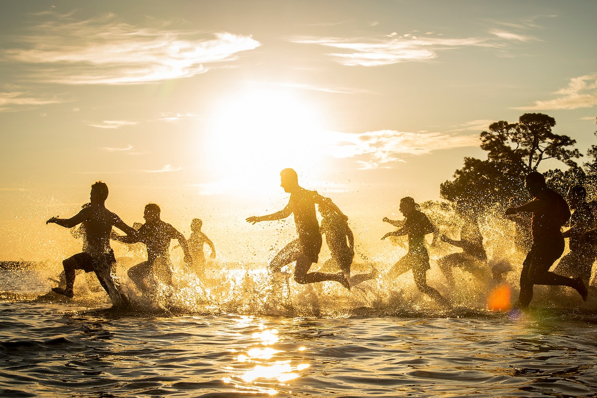 Airmen run in cold bay water during a sunset.