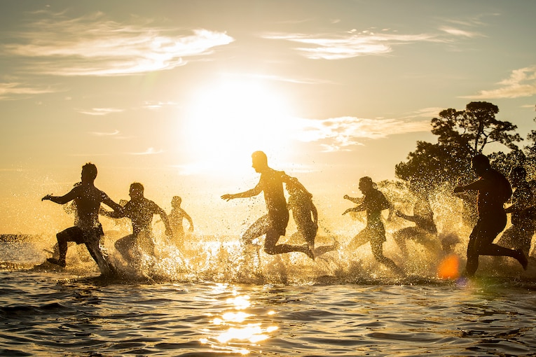 Airmen run in cold water during a sunset.
