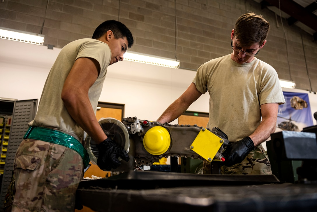 Staff Sgt. Leon Blomeley, right, 41st Helicopter Maintenance Unit craftsman, and Airman 1st Class Jonathan Flores, 41st HMU apprentice, position a gearbox during a gearbox seal replacement on a spare HH-60G Pave Hawk engine Jan. 15, 2020, at Moody Air Force Base, Georgia. These repairs are performed to increase spare-part availability of HH-60G engines. This allows the 41st HMU to swiftly return aircraft to mission-capable status without delay. (U.S. Air Force photo by Senior Airman Erick Requadt)