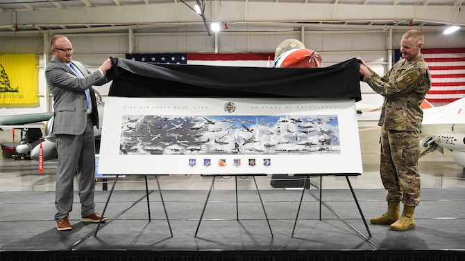 Aaron Clark at left and Col Jon Eberlan at right lift a black cloth from the top of a over-sized version of the 80th anniversary commemorative lithograph depicting the major weapons systems that have resided at Hill Air Force Base over the years.