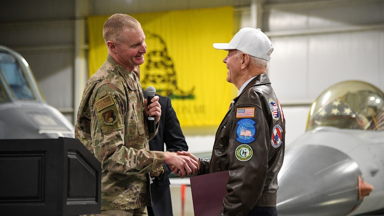 Col. Jon Eberlan at left shakes hands with retired Air Force Lt. Col. Jay Hess. Images of aircraft in the museum appear int he background.