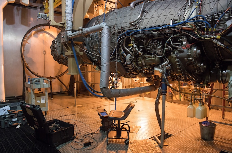 A scope sits below an F135 engine ready to be used by a technician to inspect interior elements of the engine in an Arnold Engineering Development Complex Engine Test Facility test cell at Arnold Air Force Base between test runs. The F135 is undergoing Accelerated Mission Testing in the AEDC facility and is used to power the F-35 Joint Strike Fighter Lightning II. (U.S. Air Force photo by Jill Pickett)