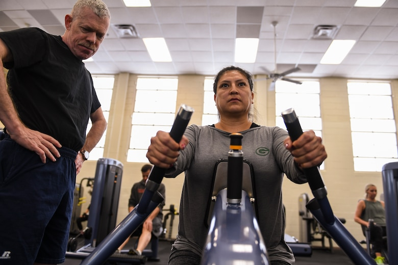 A person learns lifting techniques for the seated row weight machine.