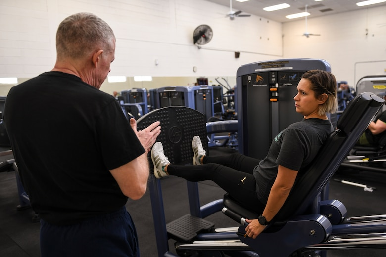 A person learns lifting techniques at a gym.