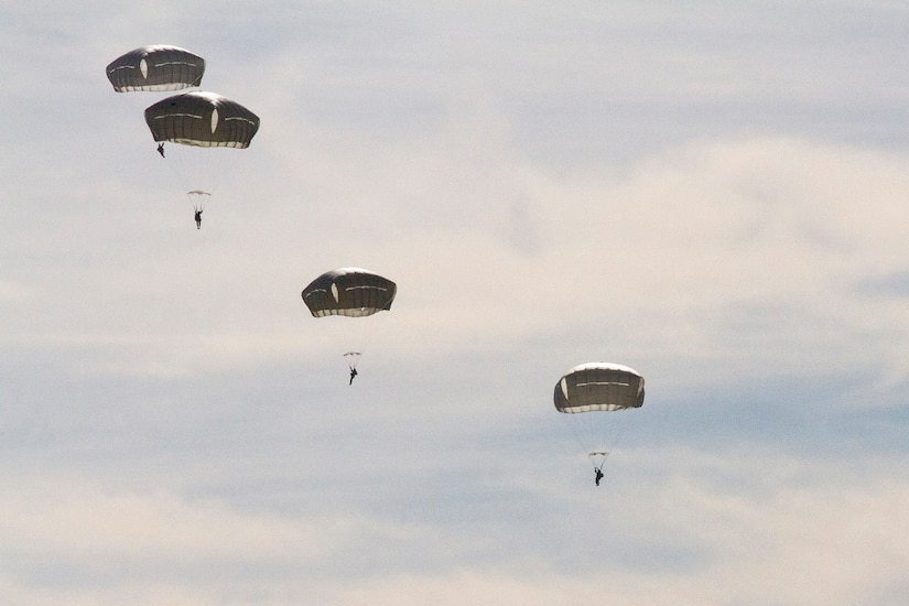 Six soldiers descend under open parachutes.