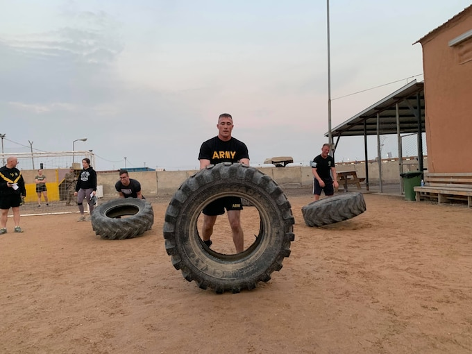 Soldiers flip large tires.