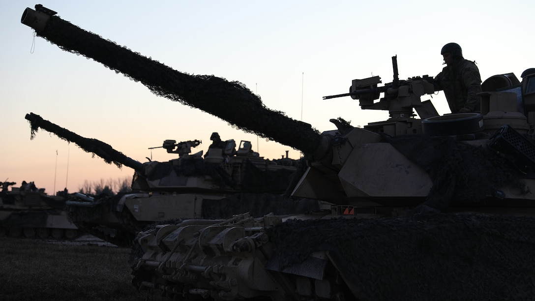 Two soldiers stand on top of two parked tanks.