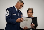 Mary O. Price is presented the Certificate of Service from Chief Master Sgt. Clinton Wilkerson, friend and presiding official of Price's retirement ceremony, Jan. 10, 2020 at Joint Base San Antonio-Randolph, Texas. Price retired after 52 years of dedicated service.