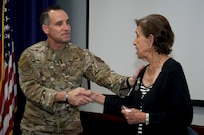 The Air Force's Personnel Center's command Chief Master Sgt. Daniel L. Hoglund congratulates Mary O. Price, with a handshake, following her retirement from federal service of 52 years.
