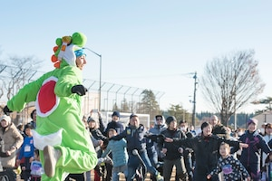 A fitness instructor leads race participants in a warmup before the run during the 39th Annual Frostbite Run, Jan.19, 2020, at Yokota Air Base, Japan.