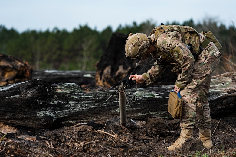 A photo of an Airman photographing a UXO