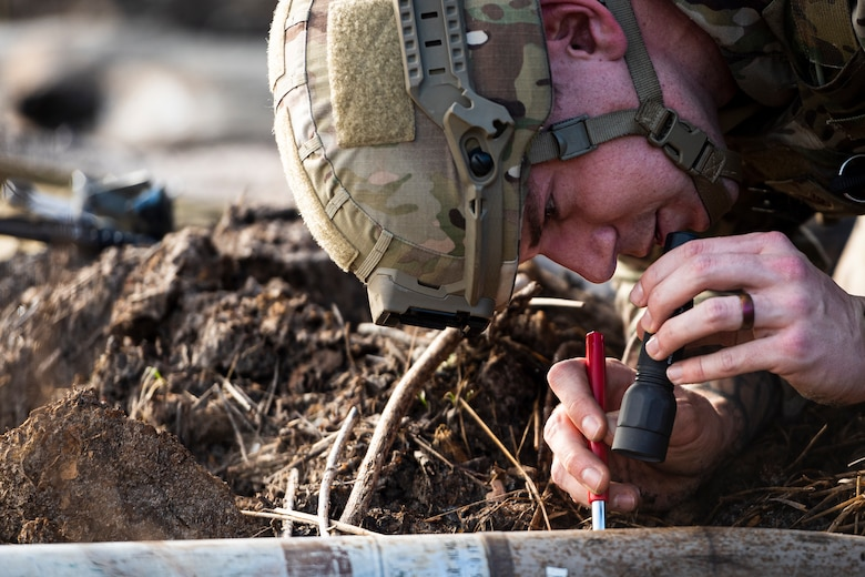 A photo of an Airman inspecting a UXO