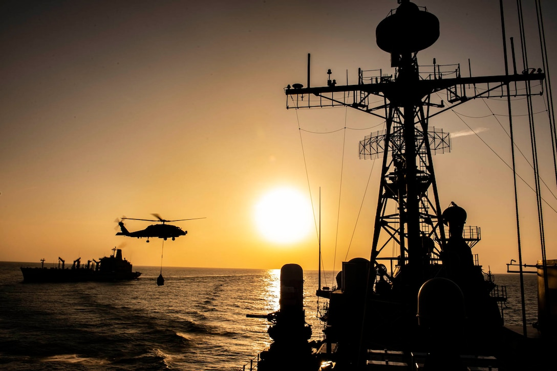 A helicopter uses a cable to carry a bundle of supplies to a military ship at twilight.