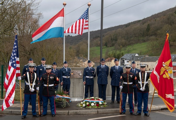 U.S. Civil Air Patrol, Spangdahlem Cadet Squadron members, back, and U.S. Marine Corp members attached to the U.S. Embassy in Luxembourg, front, pose on a bridge and in front of a plaque for U.S. Army Pfc. Vincent Festa, at Moestroff, Luxembourg, January 18, 2020. The cadets and Marines served as a honor guard detail for a ceremony dedicating the bridge to Pfc. Festa earlier that day. (U.S. Air Force photo by Senior Airman Kyle Cope)
