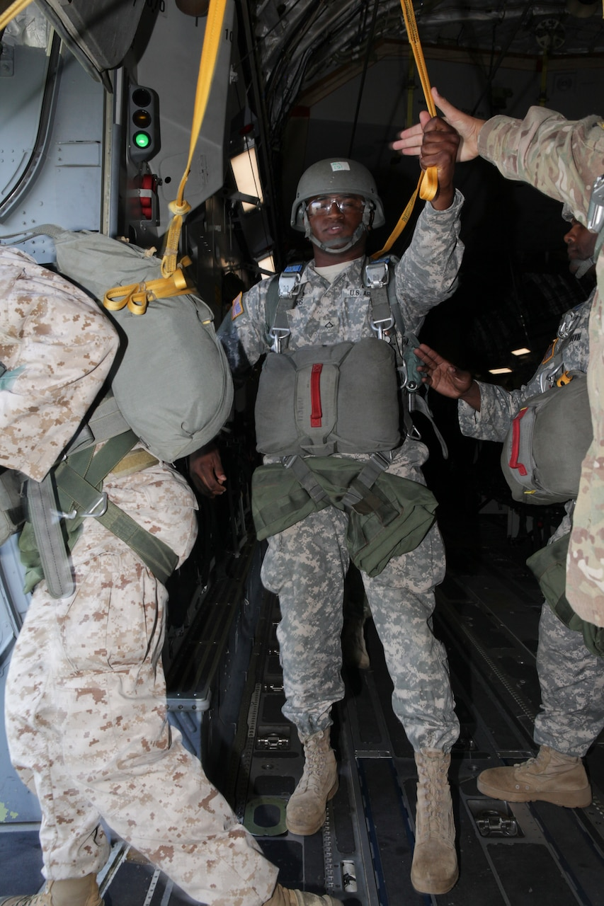 A soldier wearing a parachute hands off his static line to another soldier, as a soldier in front of him prepares to step out of the door of an airplane.