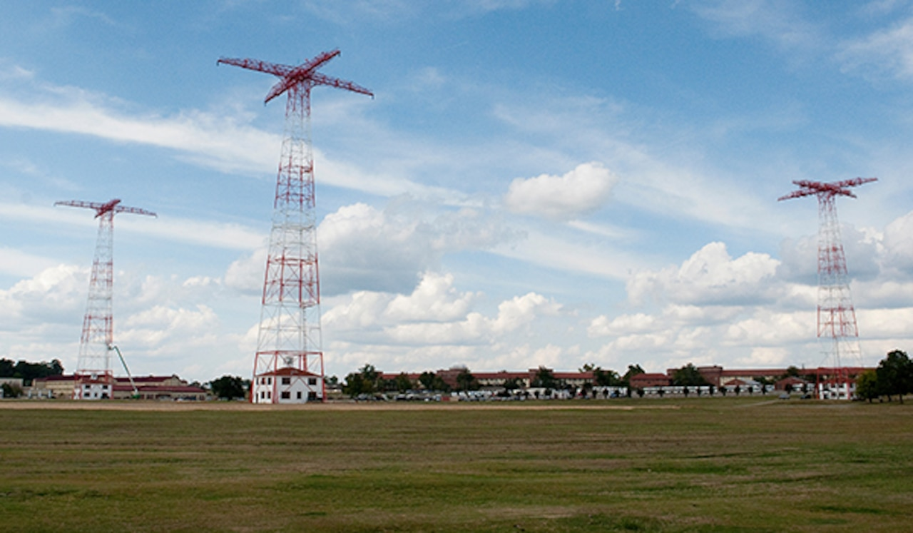 Three 250-foot red towers stand in the middle of a large field.