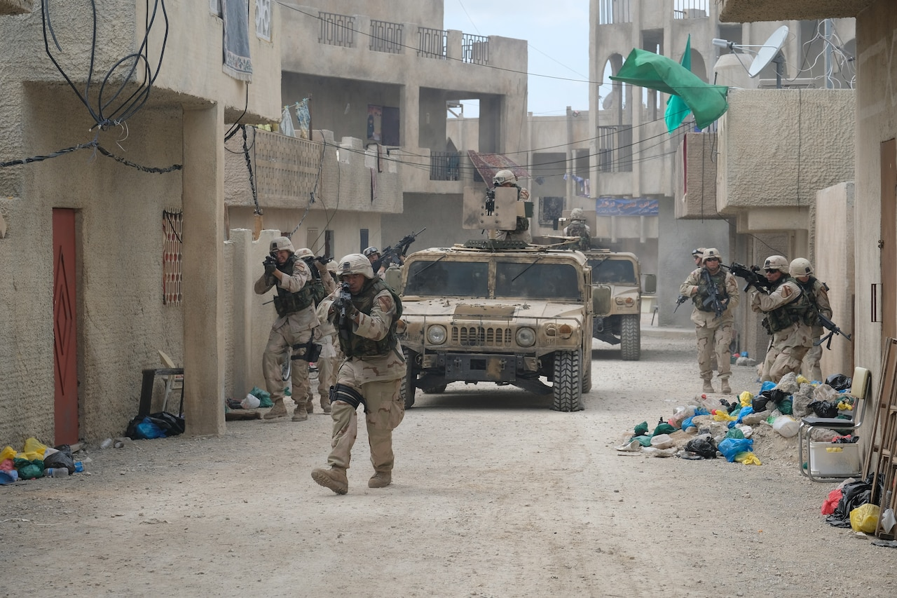 Several men dressed as soldiers walk with guns pointed on a set that looks like a street in Iraq. Two armed vehicles travel with them.