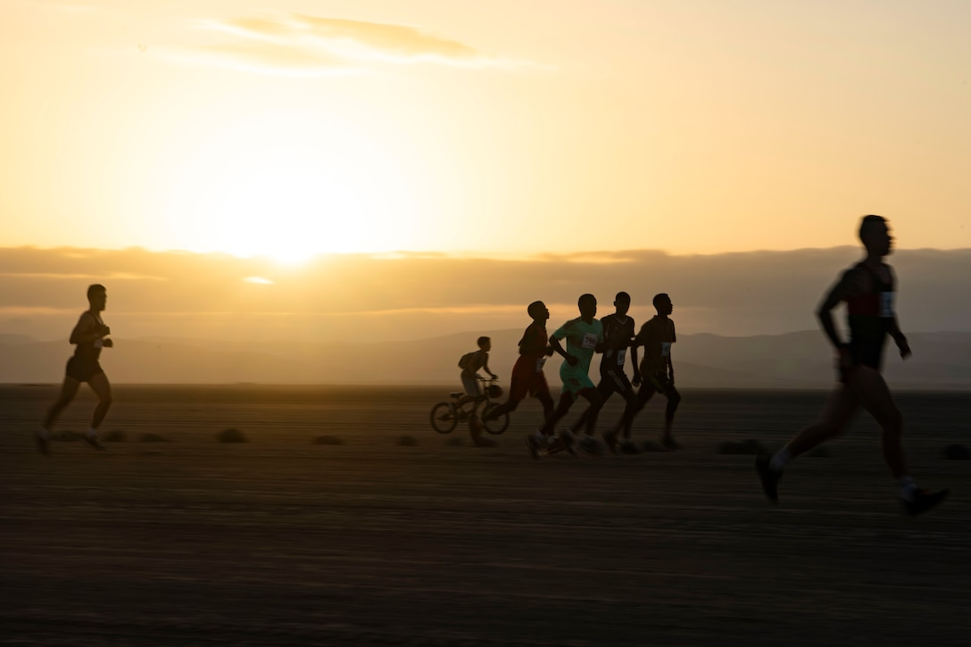 A group of people run with the sun on the horizon.