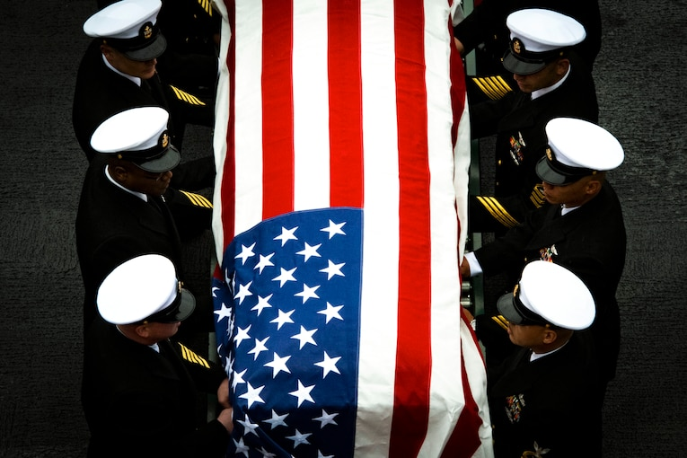 A group of sailors stand in line around a casket covered by the American flag.