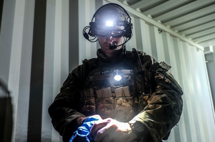 A Battlefield Surgery Team Member stands facing the camera as he removes his operating gloves in a field container serving as an operating room.
